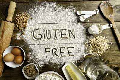 Gluten free bread ingredients and utensils on wooden background.