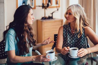 Two women having a conversation while drinking coffee.