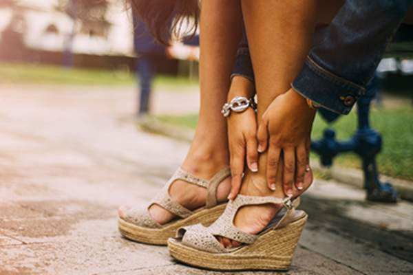 Woman wearing wedge sandals in the park.