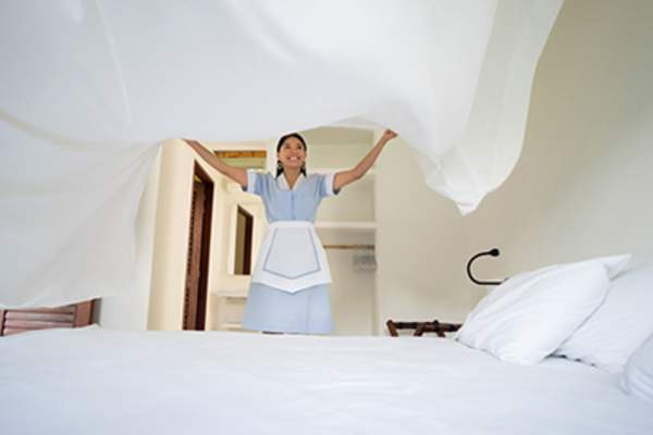 Cheerful hotel worker making up a comfortable bed.