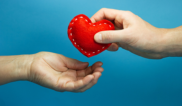 Man hand putting the red soft heart in woman hand