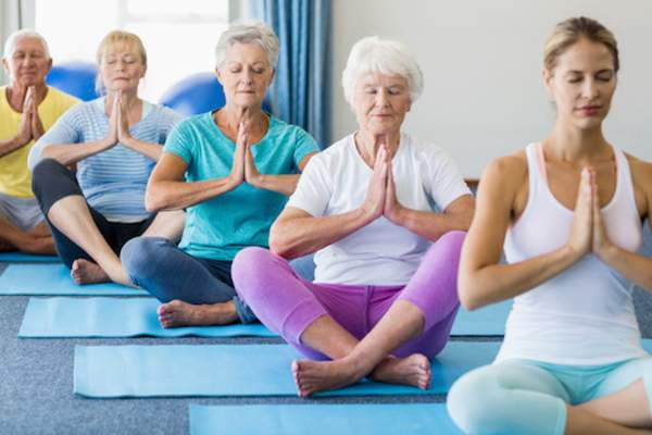 older woman doing yoga image