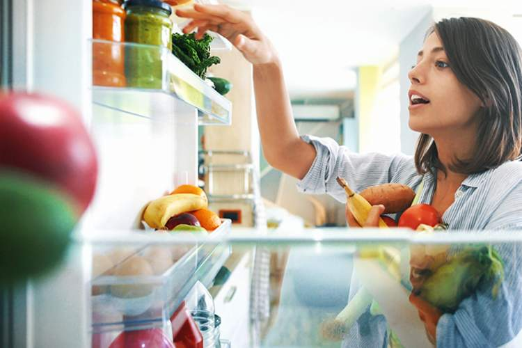 Woman getting healthy food from the fridge.
