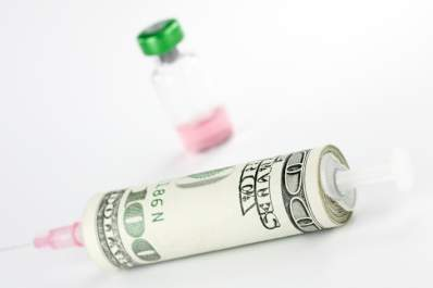 Money wrapped around syringe with vial in background.