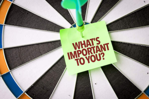 """What's Important To You?"", on sticky not attached to dartboard with dart in bullseye."