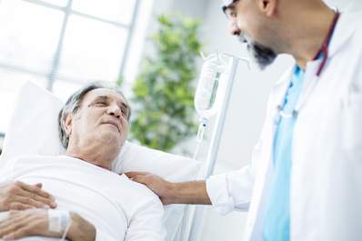 Doctor comforting a senior patient with leukemia.