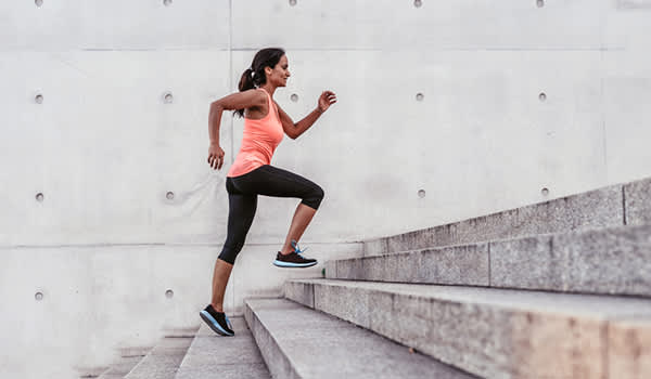 woman running upstairs exercising image
