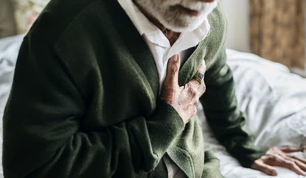 Senior man with chest pain sitting on a bed.