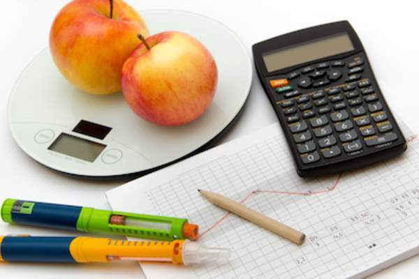 Insulin pens, apples on scale, blood sugar tracking chart and a calculator.