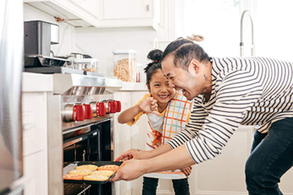 Father and daughter baking together.