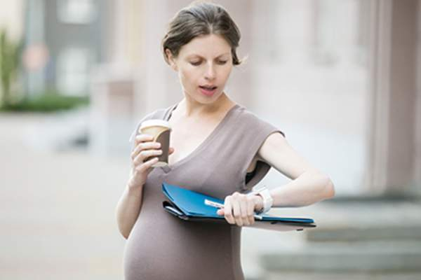 Pregnant woman carrying drink and work papers.