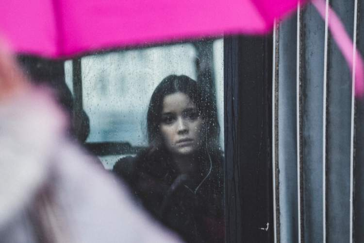 sad woman looking out window in the rain