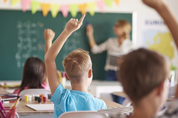 Child raising his hands in a classroom.