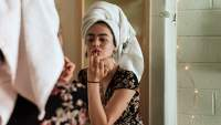 Woman applying makeup with towel wrapped around her head