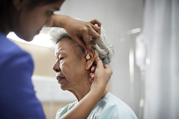Senior patient being fitted with a hearing aid.