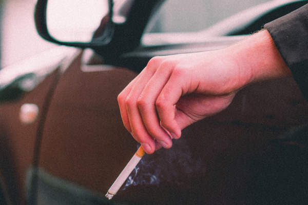 hand holding cigarette out of car window