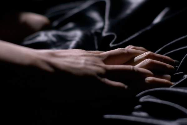 couple's hands gripping black satin sheets