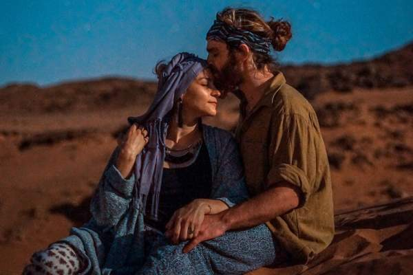couple in the desert, woman wearing head scarf