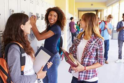 Group Of Female High School Students Talking By Lockers