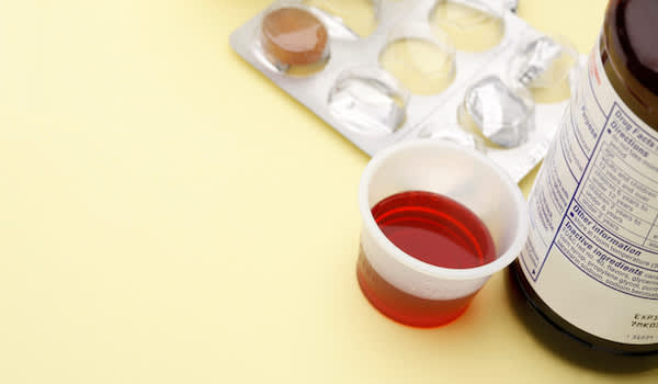 Liquid cold medicine and cold tablet in blister pack on yellow background.
