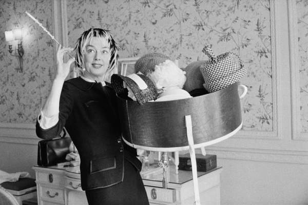 American actress Rosalind Russell holding a collection of hats, 22nd August 1958