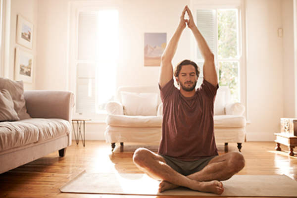 Man practicing meditation to ease stress.