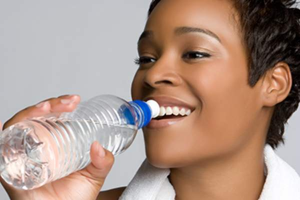Pretty young woman drinking from water bottle.