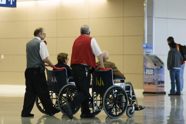 Airport employees helping elderly couple to boarding area.