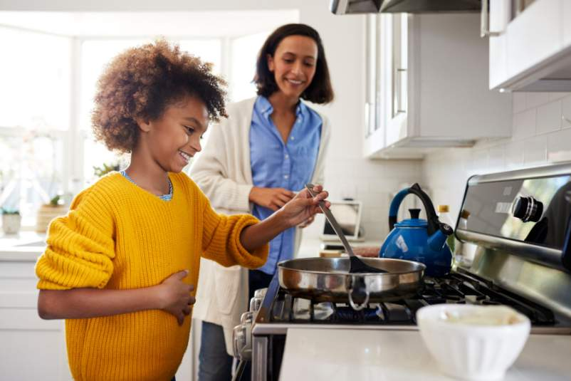 preteen girl cooking with her mom watching