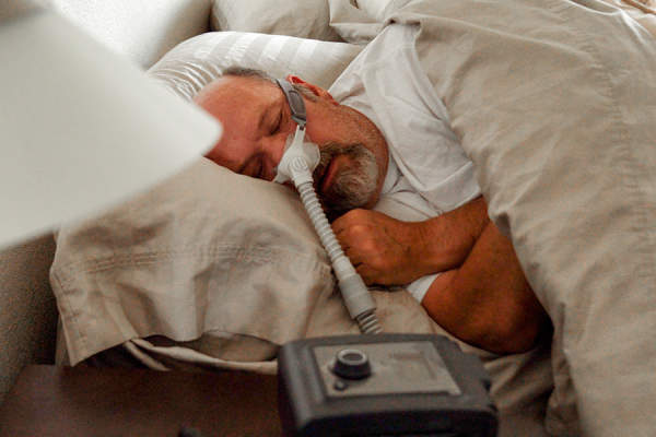 Man sleeping with a CPAP machine