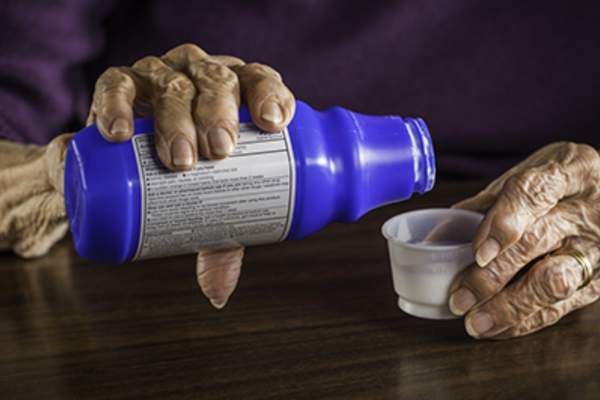 Senior woman pouring liquid laxative.