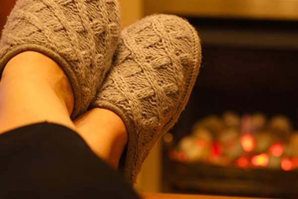 Wearing slipper in front of the fireplace.