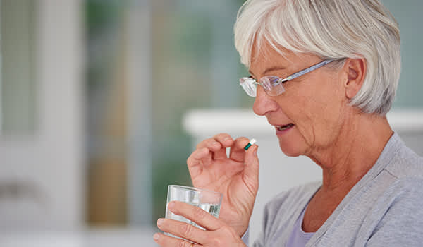 Senior woman about to swallow a pill.