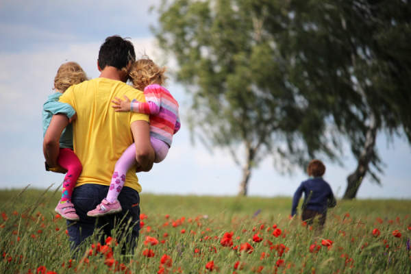 Man walking through flowers with his children