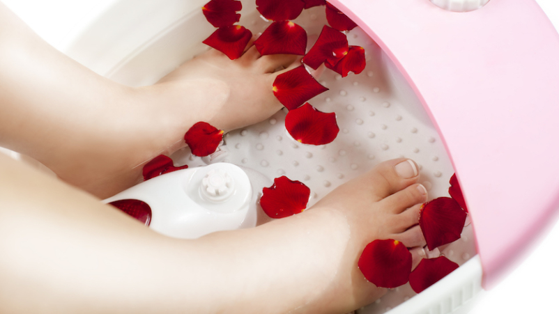 Feet in foot bath at home, with rose petals.