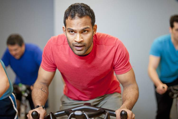 Men in spin class at gym image.