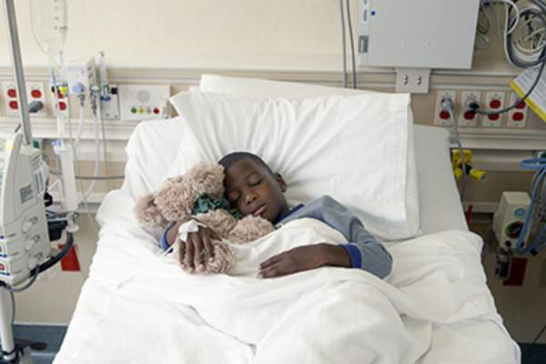 Young boy holding stuffed animal sleeping in a hospital bed.