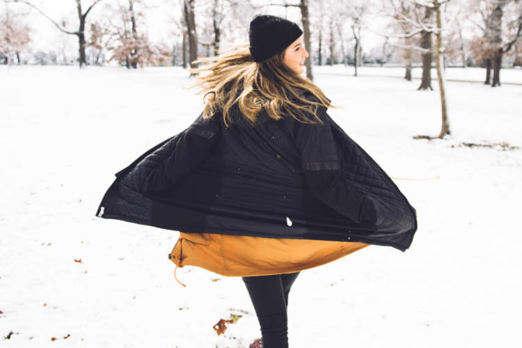 woman wearing black and yellow in the snow