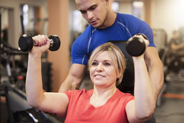 Woman strength training with a personal trainer.