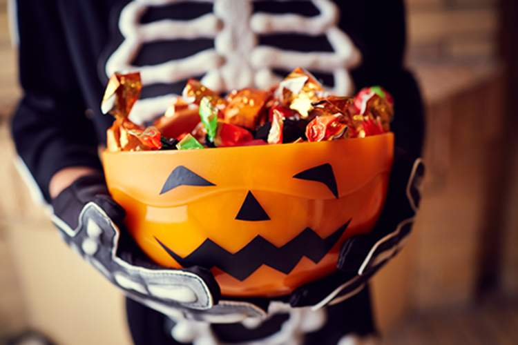 Boy in skeleton costume holding bowl full of Halloween candies.