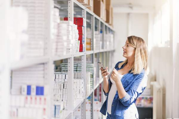 woman in pharmacy looking something up on her phone