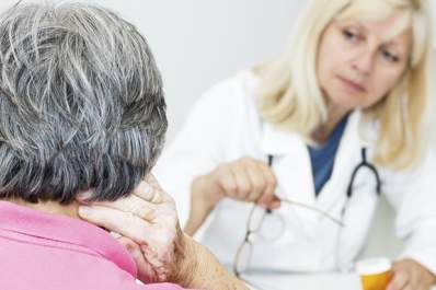 An older woman talks to her doctor about neck pain.