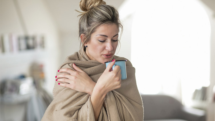 Woman who is feeling cold wrapped in a blanket and drinking tea.