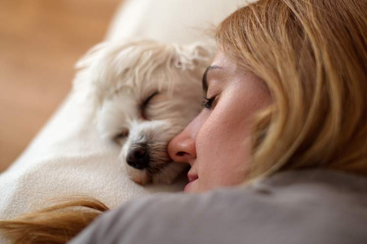 Woman getting some sleep with her small white dog.