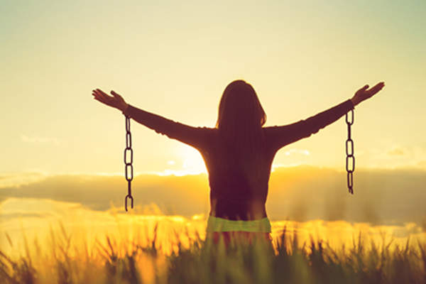 Woman free with arms raised, broken chains.