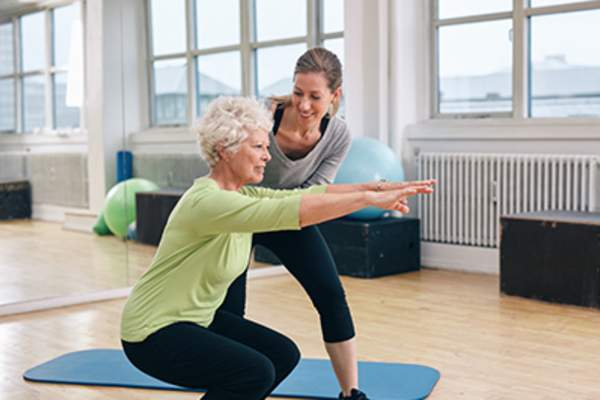 Elderly woman doing squats with her personal trainer.