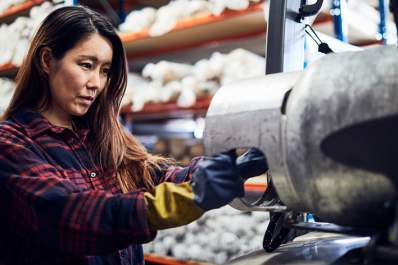 Woman at work on machine in small business.