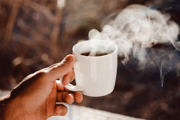hand holding steaming cup of coffee