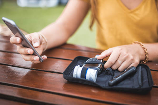 Woman with a diabetes kit and smartphone.