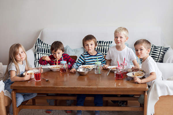 Kids eating spaghetti at coffee table.